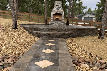 Segmental retaining wall holding up a paver patio for the gas fired fireplace in Monument Colorado